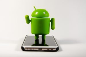 android figure standing on smartphone